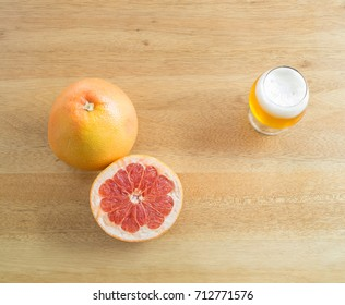 Top view - Juicy grapefruits and A glass of beer on wooden table ( space and composition for text )