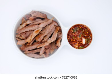 Top view of Juicy Grill pork with spicy sauce (Thai style) in white bowls on white background
