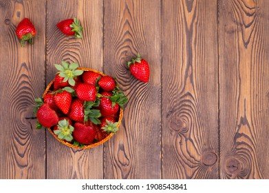 Top view of juicy strawberries in a wicker bowl on a brown shabby rustic wooden table