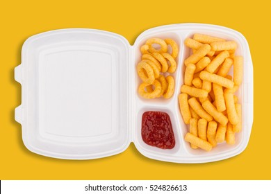 top view of junk food ingredients and a dip of ketchup in a white take away packaging box on yellow background, calories concept