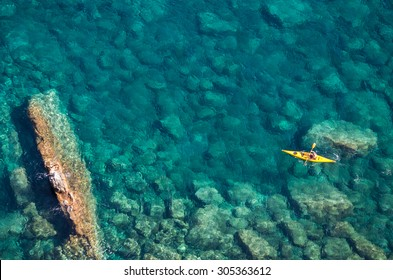 Top view of kayak boat in shallow turquoise water of Ligurian sea, Italy