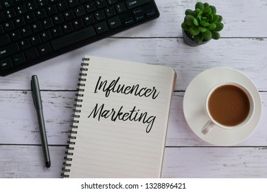 Top view of keyboard,pen,plant,coffee and notebook written with Influencer Marketing.