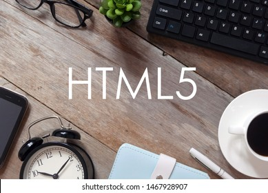 Top view of keyboard,plant,sunglasses, a cup of coffee,pen,notebook,clock and mobile phone on wooden background written with HTML5.