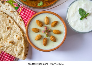 Top view of kheer with kofta salan, Spicy indian curry, Delicious meatballs with salad, bread, yogurt and colourful cushion on white background. Beautiful dessert bowl with tasty dinner.