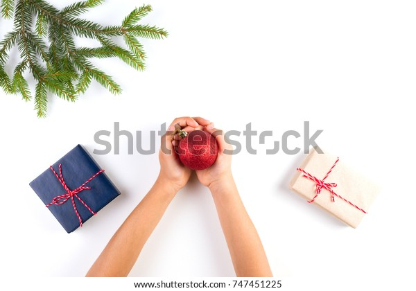 Top view of kid hands holding christmas decoration. Gift boxes and christmas tree branch on white table