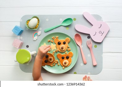 Top view of kid having her breakfast. Pink plate with funny pancakes and kid's hands on white wooden background. Flat lay.