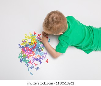 Top view of a kid playing with alphabets on a white background