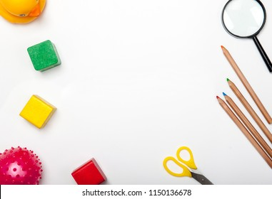 Top view of kids background with toys on white. Wooden cubes, colorful toy bricks, pencils, magnifying glass on white background. Educational toys for preschool, kindergarten or daycare. Kid's dream
