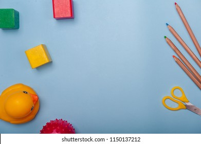 Top view of kids background with toys on white. Wooden cubes, colorful toy bricks, pencils, magnifying glass on blue background. Educational toys for preschool, kindergarten or daycare. Kid's dream