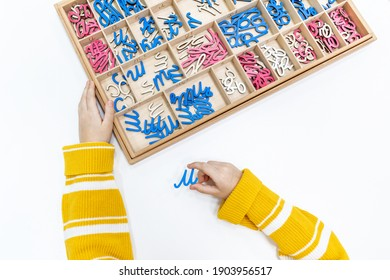 Top view of kids hands building words by using colored Montessori movable alphabet from the wooden tray on table. Concept of learning , practicing hand-eye coordination and developing motor skills.