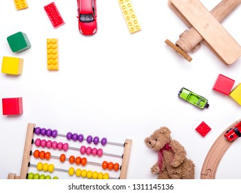 Top view of kids toys background. Wooden cubes, colorful toy bricks, scores, plane, train on white. Educational toys for preschool, kindergarten or daycare.