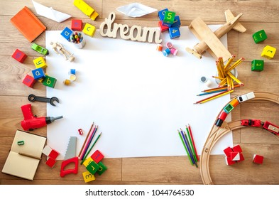 Top view of kids toys on floor on white paper. Educational toys blocks, train, railroad, plane. Toys for nursery, preschool and kindergarten or daycare. Kids toys frame on wood background.