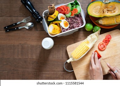 Top view kitchen table with lunch box, rice berry, boiled eggs, corn, tomatoes and cutting board preparing food. Healthy eating