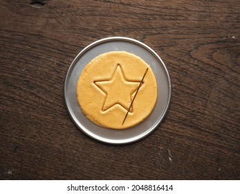 Top view Korean Dalgona or Ppopgi honeycomb sugar candy with star shape and needle on round tin tray on wooden background - Shutterstock ID 2048816414