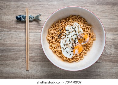 top view. Korean hot ramen special two eggs Sprinkle with seaweed Inside a cup of tile is placed on a wooden floor. Chopsticks placed next to the Ramen Cup.