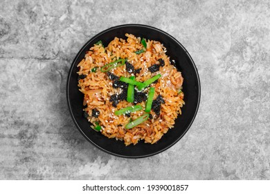 Top view Korean kimchi fried rice topping white sesame and seaweed in a black bowl on the grey concrete table, close-up shot.
