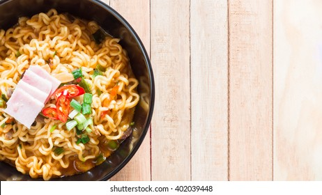 Top view of korean noodles(Ramyun) in black bowl on wooden table.