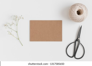 Top view of a kraft card mockup with a gypsophila and workspace accessories on a white table.