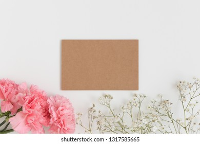 Top view of a kraft card mockup with gypsophila and a bouquet of pink carnations on a white table.
