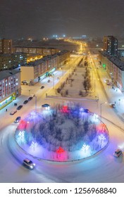 Top view of the Krasnoyarsk street in Norilsk. Snowfall on a cold winter evening in the arctic. Colorful street lighting of a large northern city. Krasnoyarsk region, Siberia, Russia.