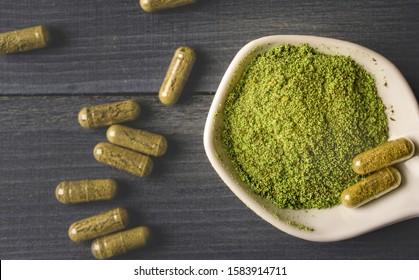Top view of Kratom powder in ceramic spoon and Kratom capsules on wooden table