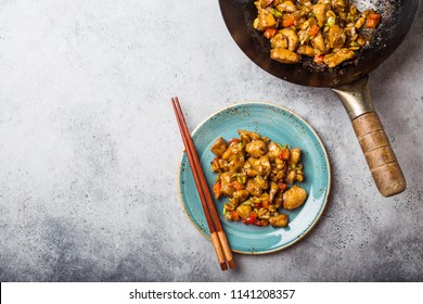 Top view of Kung Pao chicken on plate ready for eat, space for text. Stir-fried Chinese traditional dish with chicken, peanuts, vegetables, chili peppers. Chinese dinner, chopsticks, stone background