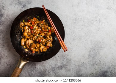 Top view of Kung Pao chicken, stir-fried Chinese traditional dish with chicken, peanuts, vegetables, chili peppers in a wok pan, space for text. Chinese dinner, chopsticks, rustic concrete background
