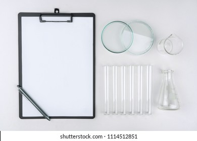 top view of laboratory equipments. A clipboard with pen, flask, test tubes, watch glass and beaker on the table