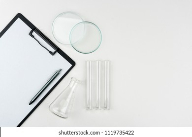 top view of laboratory equipments. A clipboard with pen, flask, test tubes and watch glass on the table