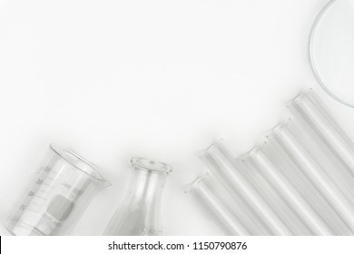top view of laboratory equipments. A flask, test tubes, watch glass and beaker on the white table