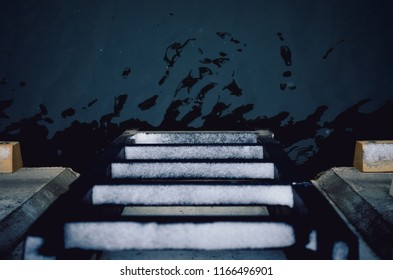 Top view of a ladder descending to water
