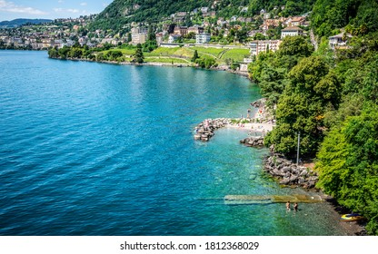 Top view of Lake Geneva shoreline in Veytaux with people swimming and Montreux city in background in Vaud Switzerland