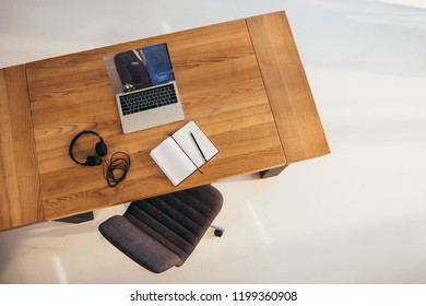 top view of laptop with booking lettering on screen, headphones and notebook on wooden table with office chair near by