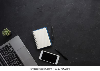 top view of a laptop,  books, pens, and smart phone on black table with copy space, business concept, objects on bottom left