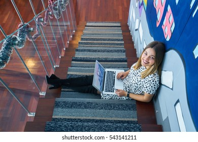 Top view of laptop in girl's hands sitting on a wooden floor with coffee