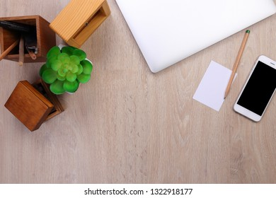 Top view laptop mockup, smartphone and office stationery with wooden background space for text