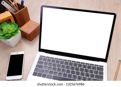 Top view laptop mockup, smartphone and office stationery on wooden background