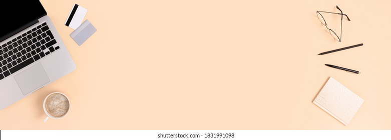 Top view of laptop, mug of coffee, stationery and credit cards on a beige background. Online shopping or e-learning concept. Banner with copy space.
