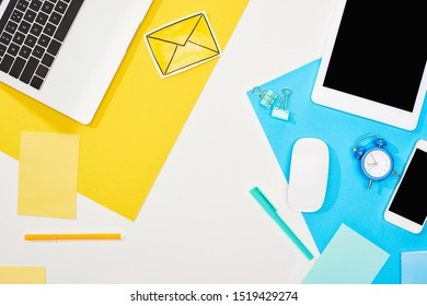 top view of laptop, smartphone, digital tablet with blank screen and computer mouse with office supplies on yellow, blue and white background