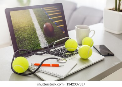 Top view of laptop, Sports Equipment, Tennis ball, Shuttlecock and glasses on the Sports administration white table.Business concept