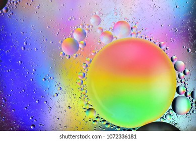 Top view of a large, backlit colorful oil drop and lots of small satellite drops floating on water.