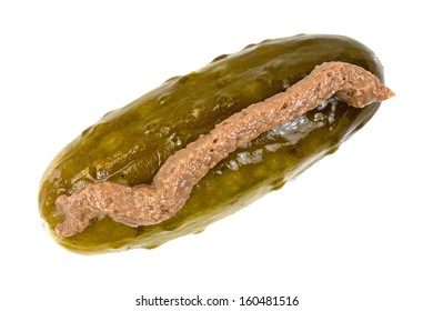 Top view of a large dill pickle with a line of anchovy paste on a white background.