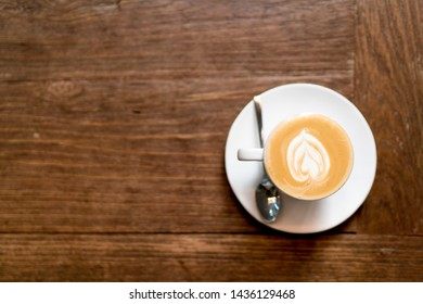 Top view latte art coffee on wooden background. heart shape latte art foam. banner space mock up for adding text