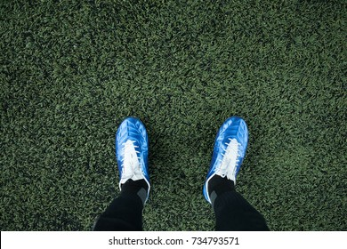 top view of leg wearing stud in the football field in a soccer game