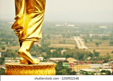 Top view legs of Golden Buddha statue standing on mountain