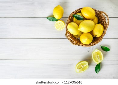 Top view of lemons fruits in wicker basket on white table. Lemon background on rustic board and copy space.