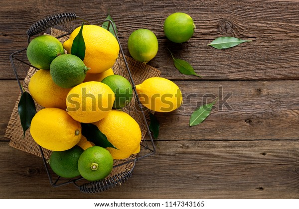 Top view of lemons and limes fruits in basket on wooden background.
