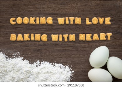 Top view of letter text collage made of cookies biscuits. Quote COOKING with love BAKING with heart putting on baking background with eggs and flour on vintage natural wood kitchen table.