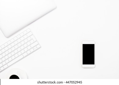 Top view of light desktop blank smartphone, coffee cup, computer keyboard and closed laptop. Mock up