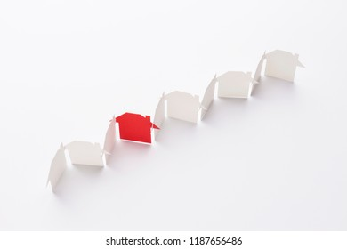 top view of line linked of paper cutout houses with red one on white background